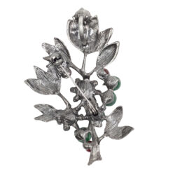 Back image of silver brooch with green and red stones