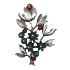 Image of silver flower brooch with green and red stones