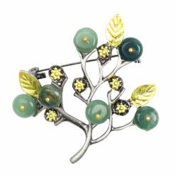 Image of silver twig brooch with green stones and yellow leaves