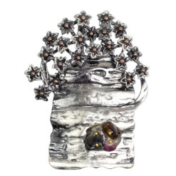 Photo of silver watering can with flowers brooch