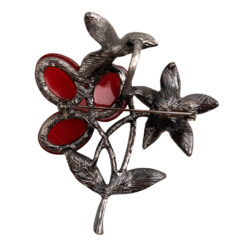 Back image of black silver brooch with flowers and red stones