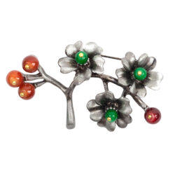 Image of silver flower brooch with orange and green stones